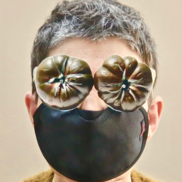 woman with short grey hair wearing tomatoes collaged onto her glasses and a black eye mask over her moth and nose